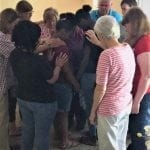 volunteers and staff in group prayer over client